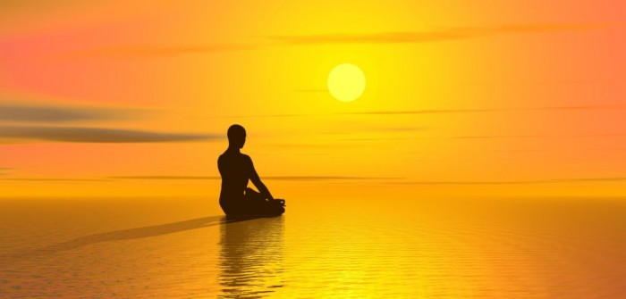 Man meditating in front of the sun and upon ocean by beautiful sunset